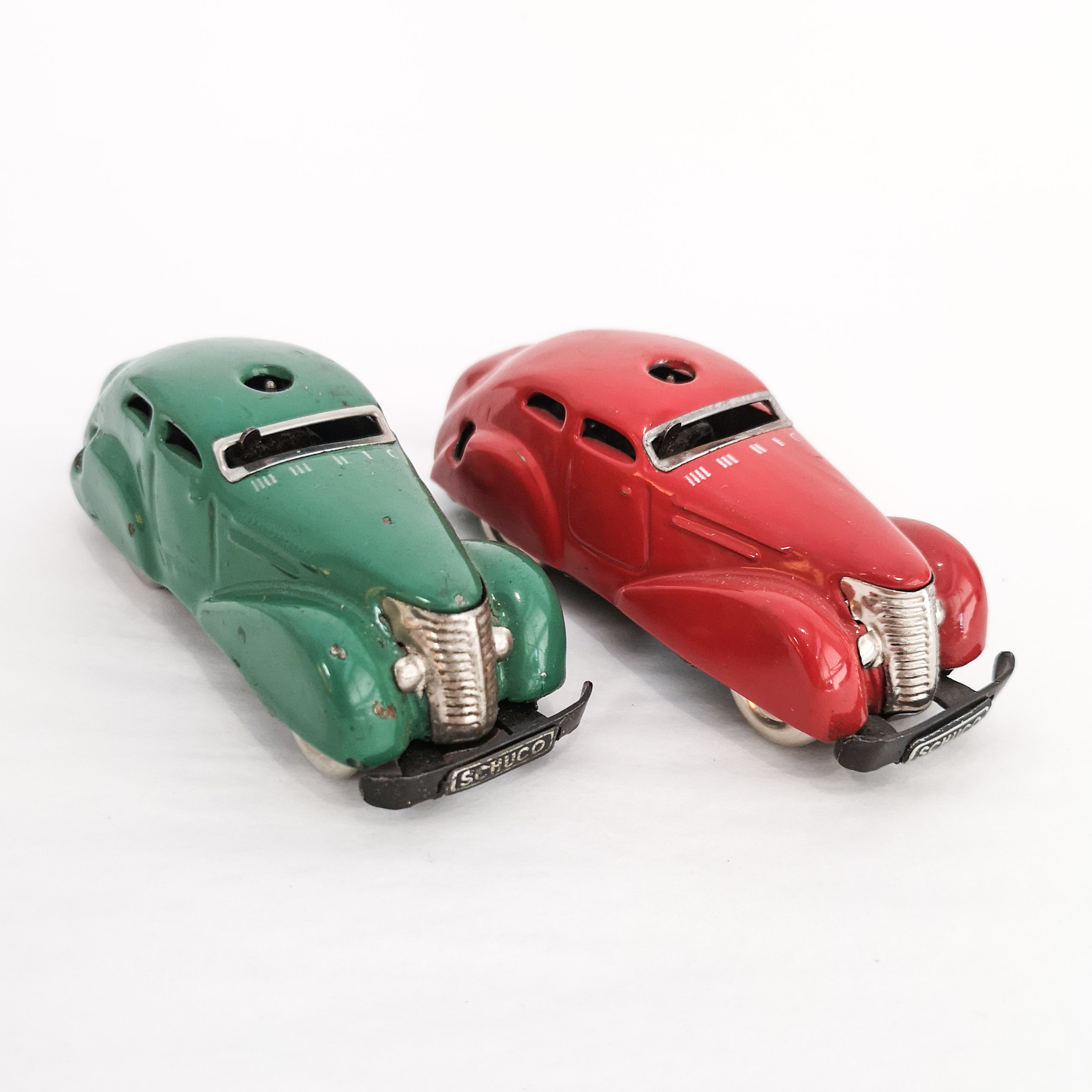 Green and red Schuco Telesteering clockwork cars, featuring 4-speed gear and stopping lever. 1.5
