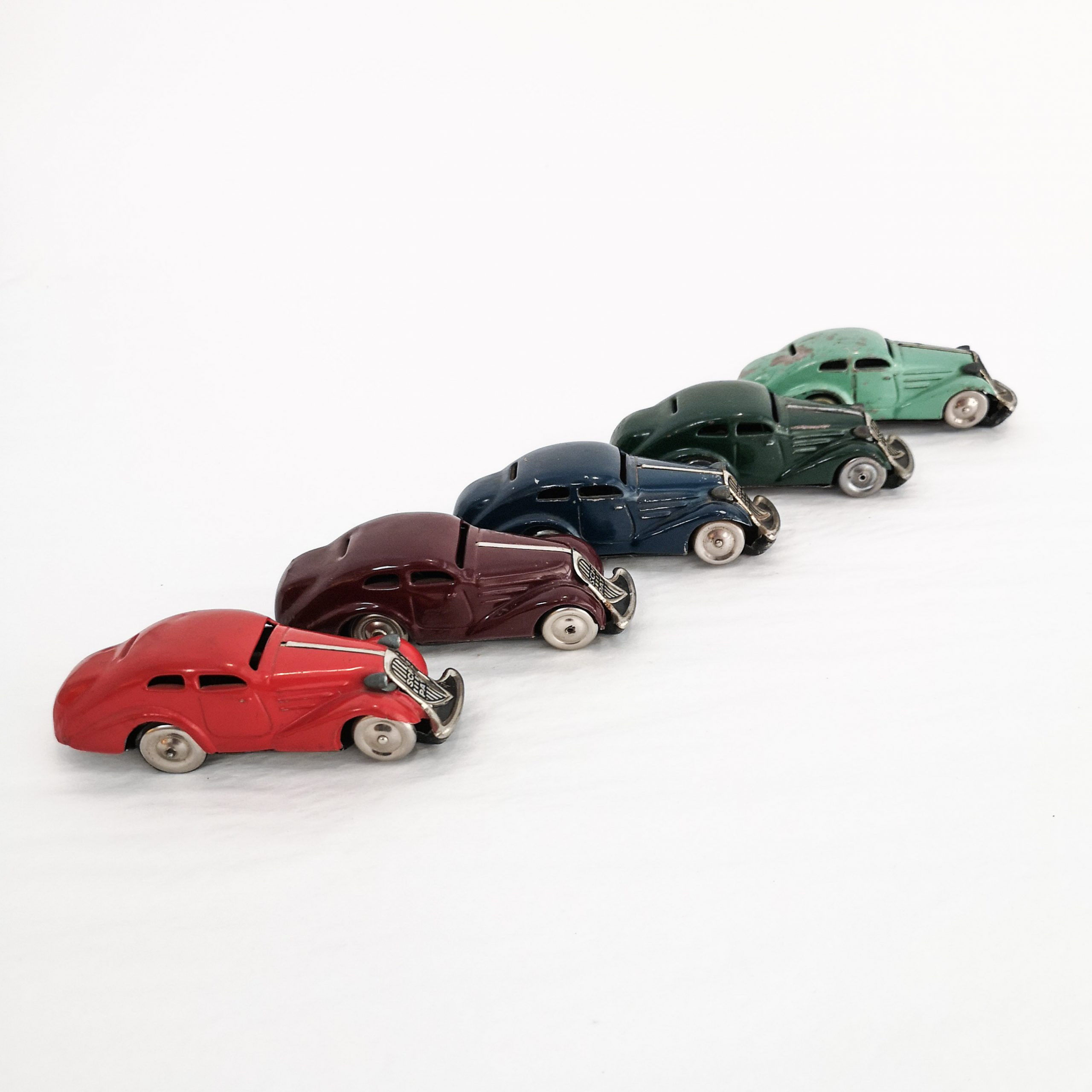 Colourful fleet of Schuco Patent Auto tinplate clockwork cars with turn-back feature. 1.5