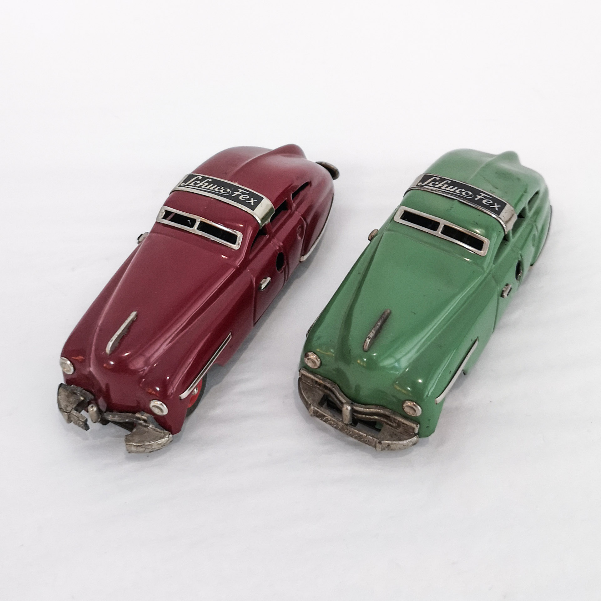 Maroon and green Schuco Fex tinplate clockwork cars with rollover feature. Made in US Zone Germany, ca. 1950s.