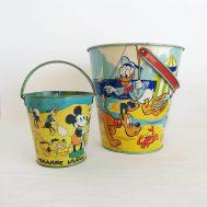 "Disney tin-litho beach pails. Treasure Island pail manufactured by Ohio Art Co, c. 1960. Donald Duck pail manufactured by J. Chein, c. 1950. 5"" tall & 8.6"" tall. ID#4175/3485"