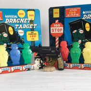 """Two Dragnet tin-litho abd plastic shooting galleries by Knickerbocker, ca. 1955, and one spring-loaded, cork-shooting pistol with original, unopened bag of corks. 11"""" tall."""
