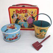 Popeye Tin, Lunchbox & Sand Pail. Tin  manufactured by K.F.S., c. 1966. Lunchbox manufactured by Aladdin, c. 1980. Sand pail manufactured by K.F.S., c. 1936.  All tin-litho. made in USA.