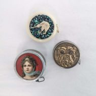 """Assorted vintage tape measures. The one featuring the young woman was an advertising novelty for F. Sutherland Queen Quality Shoe, in St. Thomas, Ontario. Tin, brass, plastic. Approx 1.5"""" diameter each."""