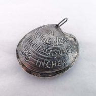 """Clam Shell Tape Measure. Front reads """"A LITTLE NECK THAT MEASURES 36 INCHES"""".  The back depicts Massacre Monument in Chicago.  Sterling silver, 1.9"""" wide."""