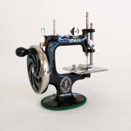 This American-made Singer sewing machine dates to c. 1936 and is complete with a metal case of replacement needles, a thorough instruction guide, and a clamp to secure the machine to a table.